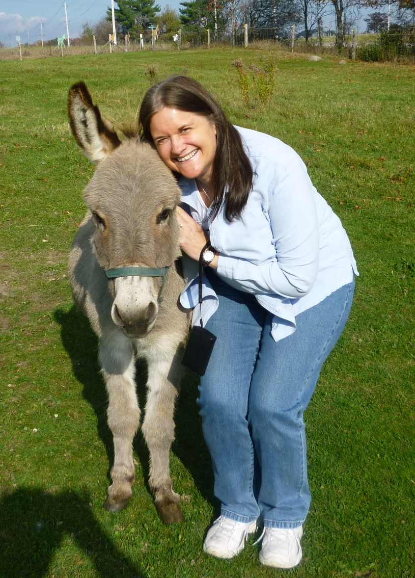 Volunteer Lynn receiving a hug from miniature donkey Jonathon Cupcake